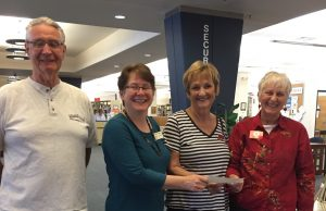 Presenting a $500.00 check to friends of the Library for the children's reading progam is Wayne & Mary Gauld members of Relics & Rods Car Club.